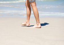 Man walking barefoot on white sand beach Royalty Free Stock Photos