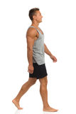 Man Walking Barefoot. Young man in black shorts and gray shirt walking barefoot. Side view. Full length studio shot isolated on white Royalty Free Stock Image