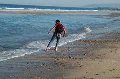 Man walking on the beach. A young man walking and getting his feet wet on the sea water Stock Photos