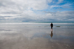 Man walking on beach Stock Images