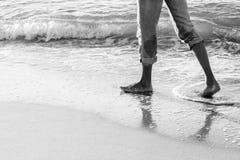 Man walking on a beach. Adult man walking on he sea wave sand sunrice beach black and white Stock Image