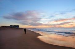 Man walking on beach at beautiful sunrise. Royalty Free Stock Photo