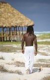 Man walking on the beach in cuba. Black man walking on the beach over wood umbrella Royalty Free Stock Image