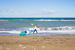 Man walking on the beach with kayak. Traveling by sea. Leisure activities on the water. Royalty Free Stock Images