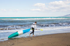 Man walking on the beach with kayak. Traveling by sea. Leisure activities on the water. Royalty Free Stock Photos