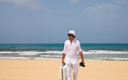 Man walking on a beach with luggage Stock Image