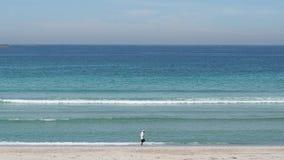 Man walking on the beach stock video
