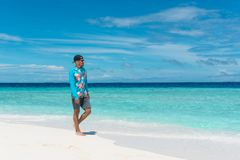 Man walking on beach with transparent water of ocean in Maldives. Man walking on beach with pure transparent water of ocean in Maldives Royalty Free Stock Photography