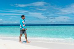 Man walking on beach with transparent water of ocean in Maldives. Man walking on beach with pure transparent water of ocean in Maldives Stock Images