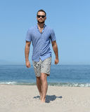 Man walking beach. Man in shorts and blue shirt walking along sandy beach with sunglasses Stock Images