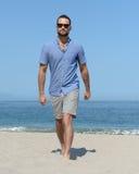 Man walking beach Stock Images