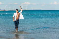 Man walking on the beach. A young man in an unbuttoned white shirt on the beach. Foot-in-the water, and pants. Male athletic build. Series stock images