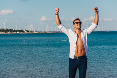 Man walking on the beach. A young man in an unbuttoned white shirt on the beach. Foot-in-the water, and pants. Male athletic build. Series Stock Photos