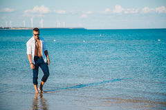 Man walking on the beach. A young man in an unbuttoned white shirt on the beach. Foot-in-the water, and pants. Male athletic build. Series Royalty Free Stock Photo