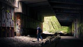 Man Walking Beneath Overpass With Graffiti stock footage