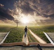 Man walking on Bible. Man walking on a Bible towards a cross royalty free stock photo