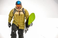 Man walking with the black and green snowboard in the mountain r stock photos