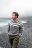 Man walking on black sand beach on Iceland. Wearing Icelandic sweater. Handsome good-looking male model looking pensive at ocean sea Royalty Free Stock Image