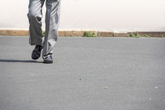 Man walking. Man in black shoes and gray trousers, walking down the street Royalty Free Stock Image