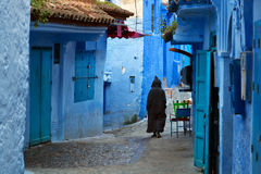 Man walking in the blue medina of Chefchaouen, Morocco Royalty Free Stock Image