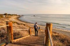 Man walking at boardwalk to beach, Malibu. Stock Photos