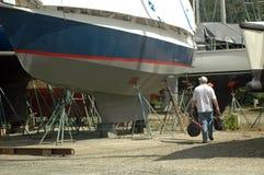 Man walking in boatyard. Man walking next to sailboat in boatyard Stock Photos