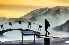 A man walking on the bridge in blue lagoon in winter. A bridge, mountains at the sunset in Blue lagoon, a man`s silhouette Royalty Free Stock Photography