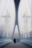 Man walking on bridge. Man crossing the bridge going for a work in a foggy morning Stock Images