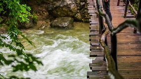Man Walking On Bridge Hanging Above Rough River. In the frame there is a man walking on wooden bridge hanging above rough river with stones and swinging to the stock video