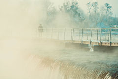 Man  walking on the bridge over river  winter. Man in jacket and cap walking along the icy bridge across the river, from which is dripping or fog early in the Stock Photos