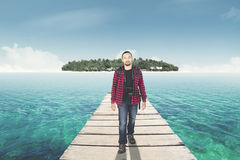 Man walking on the bridge toward island. Young afro man wearing casual clothes, walking on the wooden bridge toward island Royalty Free Stock Photography