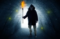 Man walking with burning flambeau in a dark tunnel stock images