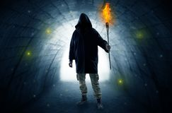 Man walking with burning flambeau in a dark tunnel stock image