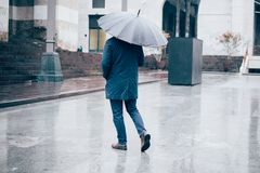 Man walking in the city with umbrella on rainy day Stock Images