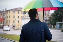 Rainy day in the city and businessman holding umbrella Royalty Free Stock Images