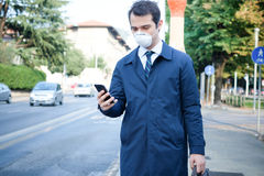 Man walking in the city wearing protection mask against smog air Royalty Free Stock Photography