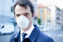 Man wearing mask against smog air pollution. Man walking in the city wearing protection mask against smog air pollution royalty free stock images