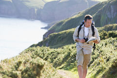 Man walking on cliff side path looking at map Stock Images