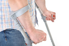 Man walking with a crutch. Against white background Stock Images