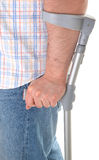 Man walking with a crutch Stock Photo