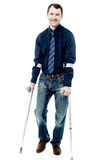 Man walking with crutches isolated on white Stock Photos