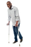 Man walking with crutches isolated on a white. Smiling man with crutches trying to walk Royalty Free Stock Images