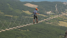 Man Walking a Dangerous Suspension Bridge stock video footage