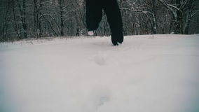 Man Walking in the Deep Snow in the Winter Forest at Snowy Day. Slow Motion stock video footage
