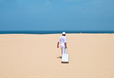 Man walking at a desert with luggage Royalty Free Stock Images