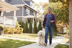 Free Man Walking Dog Along Suburban Street Stock Photography - 108957022