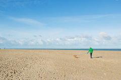 Man walking with dog at the beach Royalty Free Stock Photo