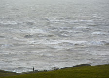 Man walking dog. On a cliff edge over rough sea Stock Photography