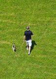 Man Walking Dog in a Grassy Field. Image taken from above, man and his dog walking in a grassy meadow royalty free stock photography