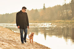 Man walking with dog near the river Royalty Free Stock Photos